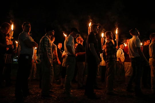 FILE - In this Aug. 11, 2017, file photo, multiple white nationalist groups march with torches through the University of Virginia campus in Charlottesville, Va. Multiple arrests have been made in connection with a white nationalist torch-lit march and rally in Charlottesville, Virginia, last year, federal authorities said Tuesday, Oct. 2, 2018.