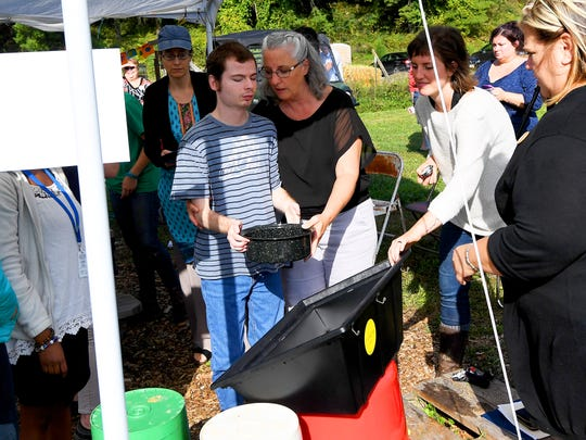 Tommy Adams, a blind adult student at the school, carries a cooking pot over to the solar oven in a class at Virginia School for the Deaf and Blind's educational urban farm on Monday, Oct. 02, 2018.