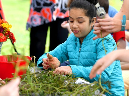 A student holds and feels a sweet potato they grew at Virginia School for the Deaf and Blind's educational urban farm on Monday, Oct. 02, 2018.