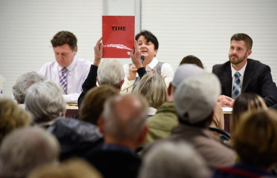 The timekeeper holds up a sign Monday, Oct. 1, during the League of Women Voters House 14A and 14B debate in St. Cloud.