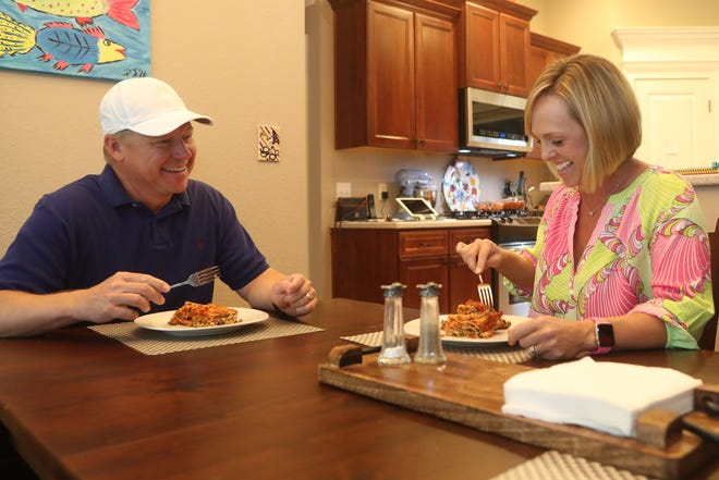 Anna Jones, local dietician, right, eats veggie lasagna with her husband Perry Jones, at their home in Tallahassee, Fla. A diet rich in whole grains, vegetables and beans plays a role in cancer prevention. As part of Breast Cancer Awareness Month, Jones prepared this No Boil Veggie Lasagna, packed with spinach, red peppers and tomatoes.