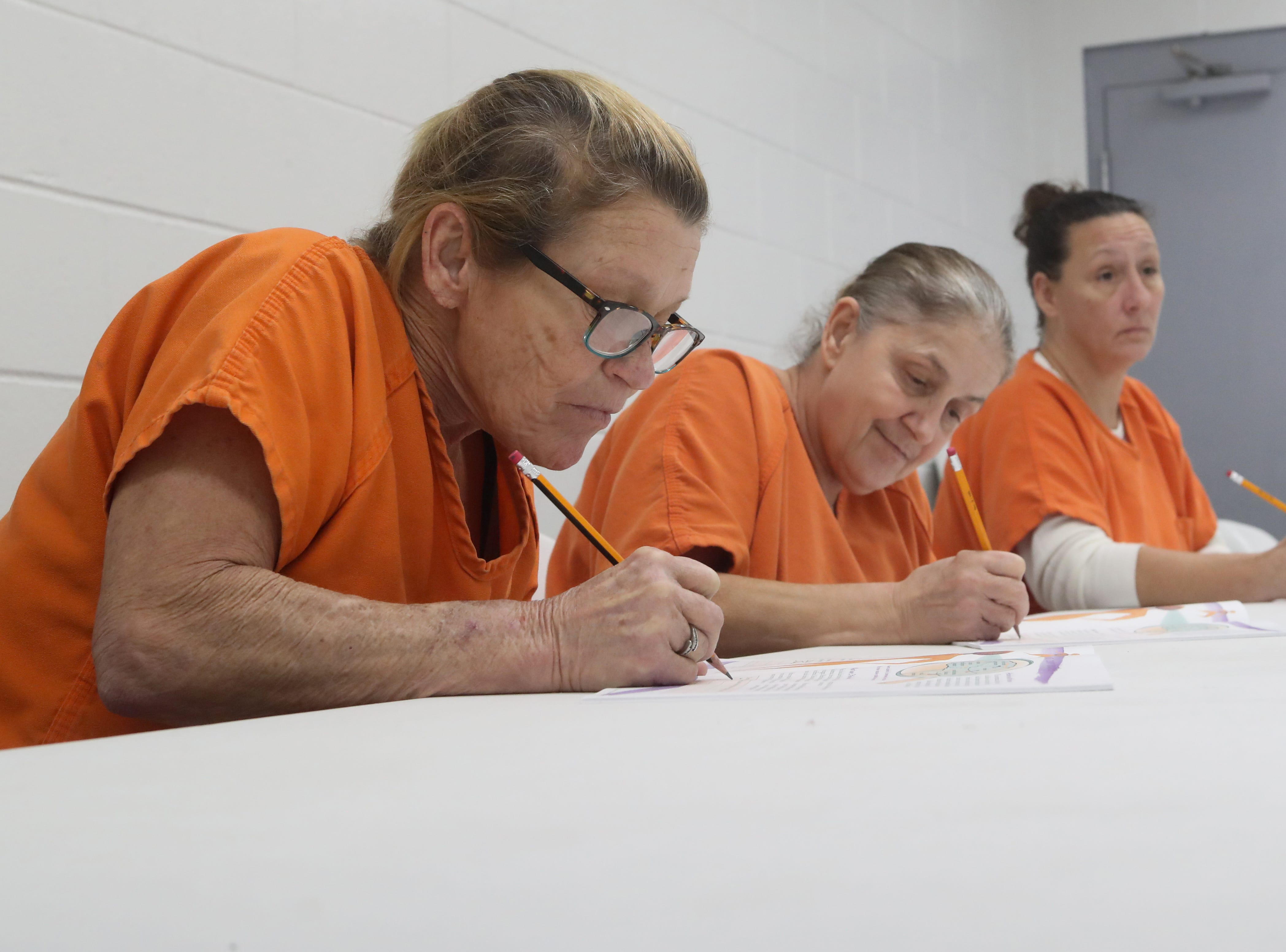 Donna Needer, Tina Davis and Tonya Seamon, inmates at the Franklin County Jail write in their workbooks during a substance abuse counseling class by DISC Village at the jail in Eastpoint, Fla. Thursday, Oct. 27, 2018.