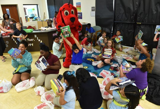 """""""I like it, I'm happy, because I got eleven free books,"""" said Juan Romero, 11, (center) holding up one of his selections as he and his fifth-grade classmates celebrate selecting eleven new books each from among hundreds of titles during Vero Beach Elementary School's Scholastic Book Magic event on Monday, October 1, 2018. """"We're going to be going through about 8,000 books by the time we're done with this week,"""" said Cynthia Emerson, principal at Vero Beach Elementary School. """"Every single kid is going to get eleven books to take home...what they want, what they choose, based on their interests, kindergarten through fifth-grade."""""""