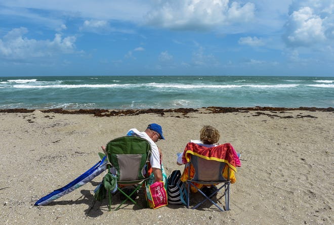 """""""Yesterday we noticed a lot of people in Jensen surfing, but not today,"""" said Luanne Sjostrom as she and her husband, Tim, both of St. Charles, Illinois, soak up some some sun Tuesday, Oct. 2, 2018, at Bathtub Reef Beach in Stuart. Martin County beaches were left unguarded Sunday afternoon after lifeguards began coughing due to a possible airborne irritant. The FWC has begun testing local waters for red tide, a marine algae, which is lethal to marine life and dangerous for humans."""