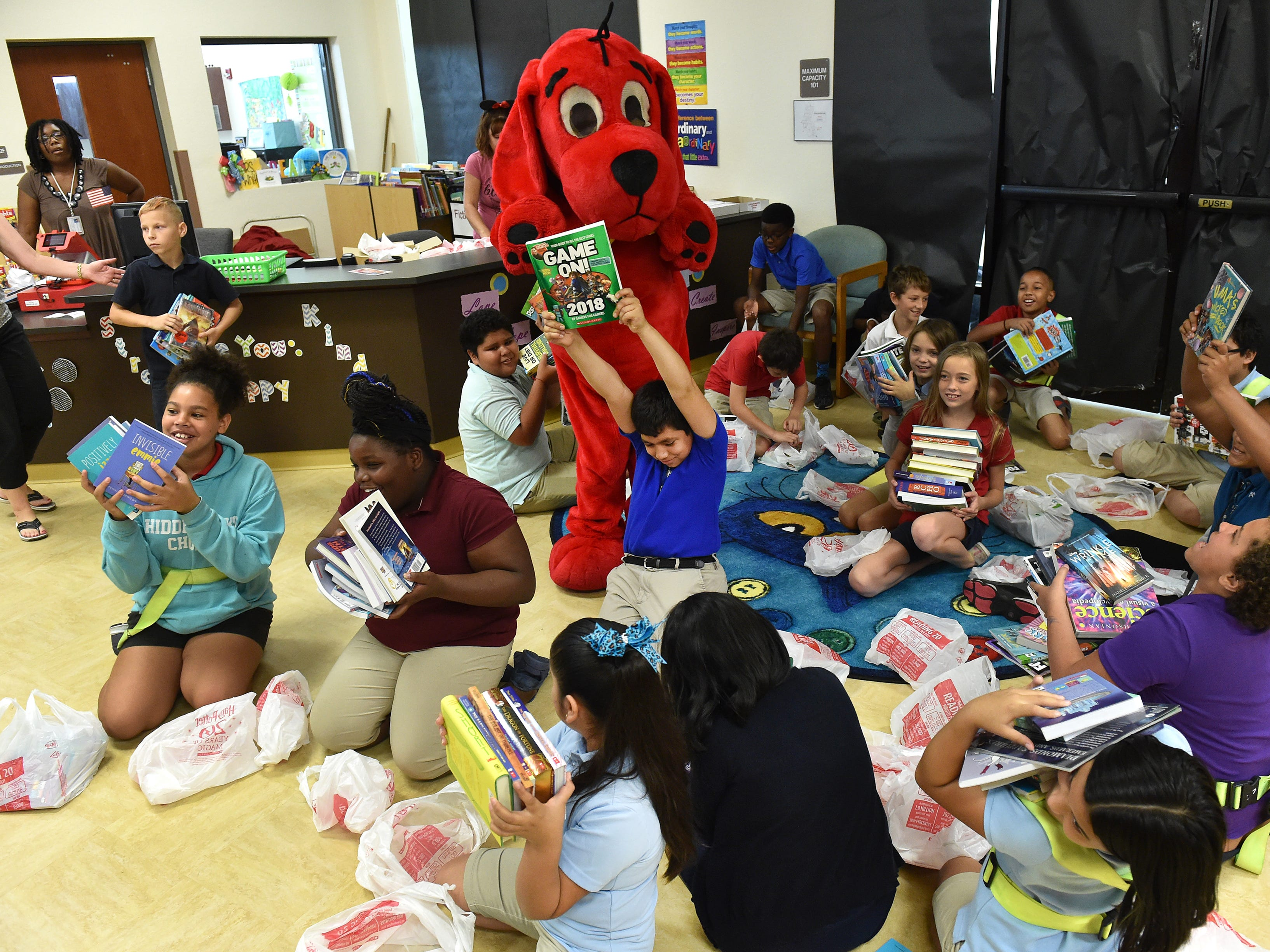 """""""I like it, I'm happy, because I got eleven free books,"""" said Juan Romero, 11, (center) holding up one of his selections as he and his fifth grade classmates celebrate selecting eleven new books each from among hundreds of titles during Vero Beach Elementary School's Scholastic Book Magic event on Monday, October 1, 2018. """"We're going to be going through about 8,000 books by the time we're done with this week,"""" said Cindy Emerson, Principal at Vero Beach Elementary. """"Every single kid is going to get eleven books to take home... what they want, what they choose, based on their interests, kindergarten through fifth grade."""""""