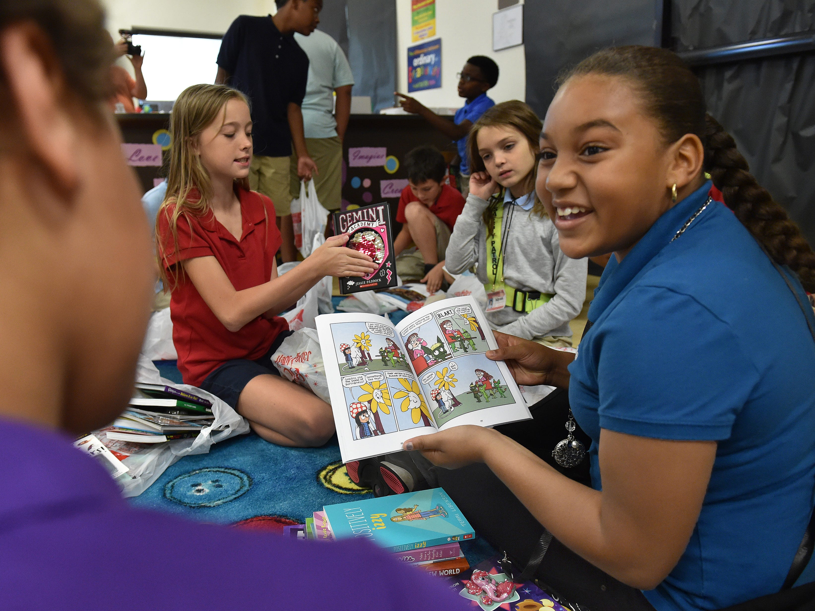 """Beyonka Florez, 10, (right) shows off a page of one of her new books to friend Aanyia Poindexter, 10, after the group of fifth grade students selected eleven new books each during Vero Beach Elementary School's Scholastic Book Magic event on Monday, October 1, 2018, inside the media center. """"It creates an experience for kids that they can be tied to emotionally forever,"""" said Cynthia Emerson, Principal at Vero Beach Elementary. """"By making this experience for them they are always going to have this positive emotional response to reading and it's giving them the actual tools that they can use at their houses to build on a foundation of literacy."""""""