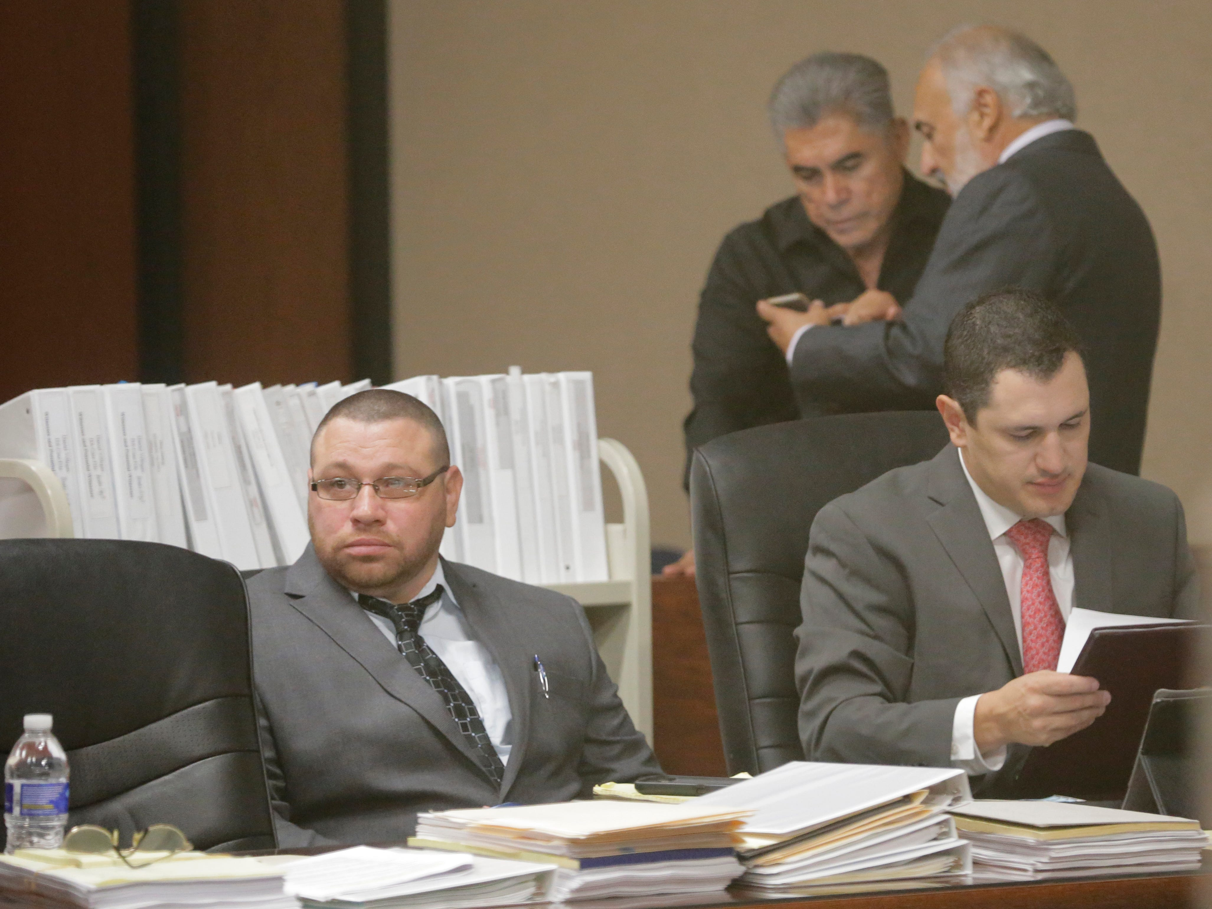 """Daniel Villegas (l) sits with one of his attorneys during opening day testimony in his third trial. Villegas is charged with Capital Murder in connection in the 1993 deaths of Armando """"Mando"""" Lazo and Bobby England. Villegas, who was 16 years old at the time, was allegedly a member of a street gang that shot at four teens, fatally striking Lazo and England on April 10, 1993. Lead attorney Joe Spencer stand sin the background with local businessman John Mimbela Sr. who has become a leading voice in the efforts to get Villegas this third trial and released from prison."""