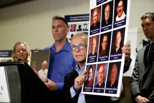 Attorney Jeff Anderson, center, holds photographs of clergy accused of sexual abuse, next to abuse survivor Tom Emens, second from left, on Tuesday in Los Angeles. Survivors of clergy sexual assault announced the filing of a nuisance lawsuit against California Roman Catholic bishops for covering up abuse.