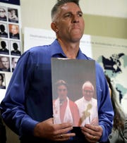 Tom Emens holds a picture of himself as a boy with Monsignor Thomas Joseph Mohan, the priest who he claims sexually abused him in the late 1970s, during a news conference on Oct. 2, 2018, in Los Angeles.