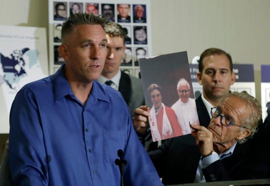 Tom Emens, left, who says he was sexually abused by a priest, speaks on his experience next to attorney Jeff Anderson on Oct. 2, 2018, in Los Angeles. Anderson is holding a photograph of Emens as a boy next to the priest who he says abused him, Monsignor Thomas Joseph Mohan.