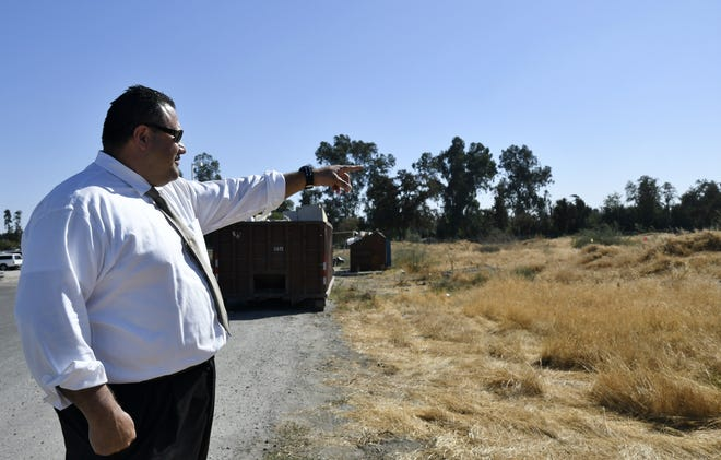 Principal Adolfo Reyes points to the site of the new Sequoia High School campus along North Woodland Street in Visalia on Monday, October 1, 2018.