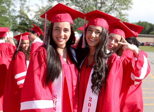 Christine Russo, left, and Hannah Sgaglio get ready to participate in Somers High School's Class of 2018 graduation.