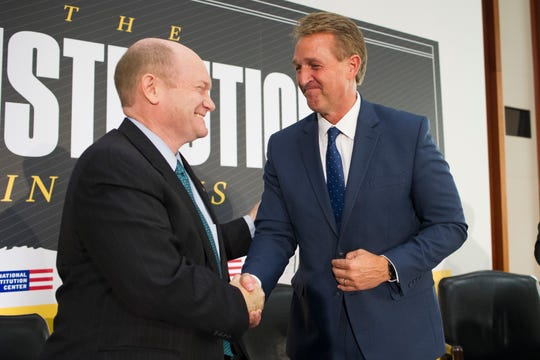 "Chris Coons, D-Del., left, shakes hands with Sen. Jeff Flake, R-Ariz., after participating in an interview at The Atlantic's ""The Constitution in Crisis"" forum in Washington, on Tuesday, Oct. 2, 2018. The forum is in partnership with National Constitution Center and Gallup."