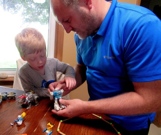 Four-year-old Harrison and Russ working with Transformers.