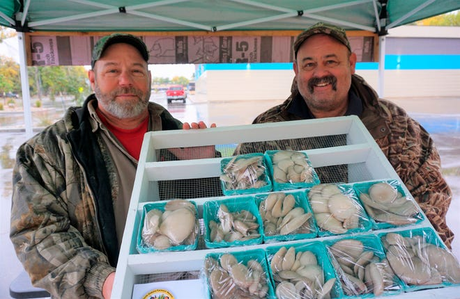 In this Sept. 20, 2018, photo, Dan, left, and Jeff Coggins hold a tray of some of the oyster mushrooms available at their farmers market booth in Minot. The brothers have found success in their second year harvesting mushrooms and selling their product at local farmers markets.