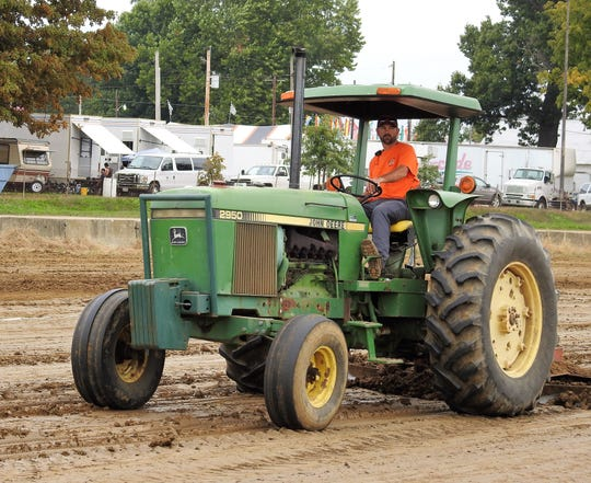 Jason Massie of the Coshocton County Fair Board helps to finish track preparations before the start of open tractor pulls Tuesday at the Coshocton County Fair.