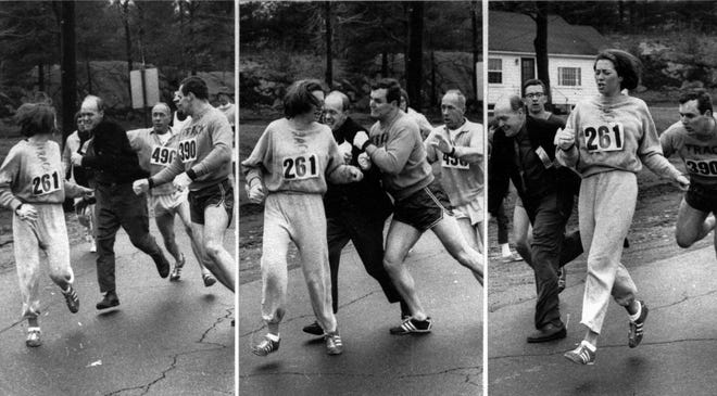 A woman, listed only as K. Switzer of Syracuse, found herself about to be thrown out of the normally all-male Boston Marathon when a husky companion, Thomas Miller of Syracuse, threw a block that tossed a race official out of the running instead, April 19, 1967 in Hopkinton, Mass.(AP PHOTO/Courtesy Boston Herald)