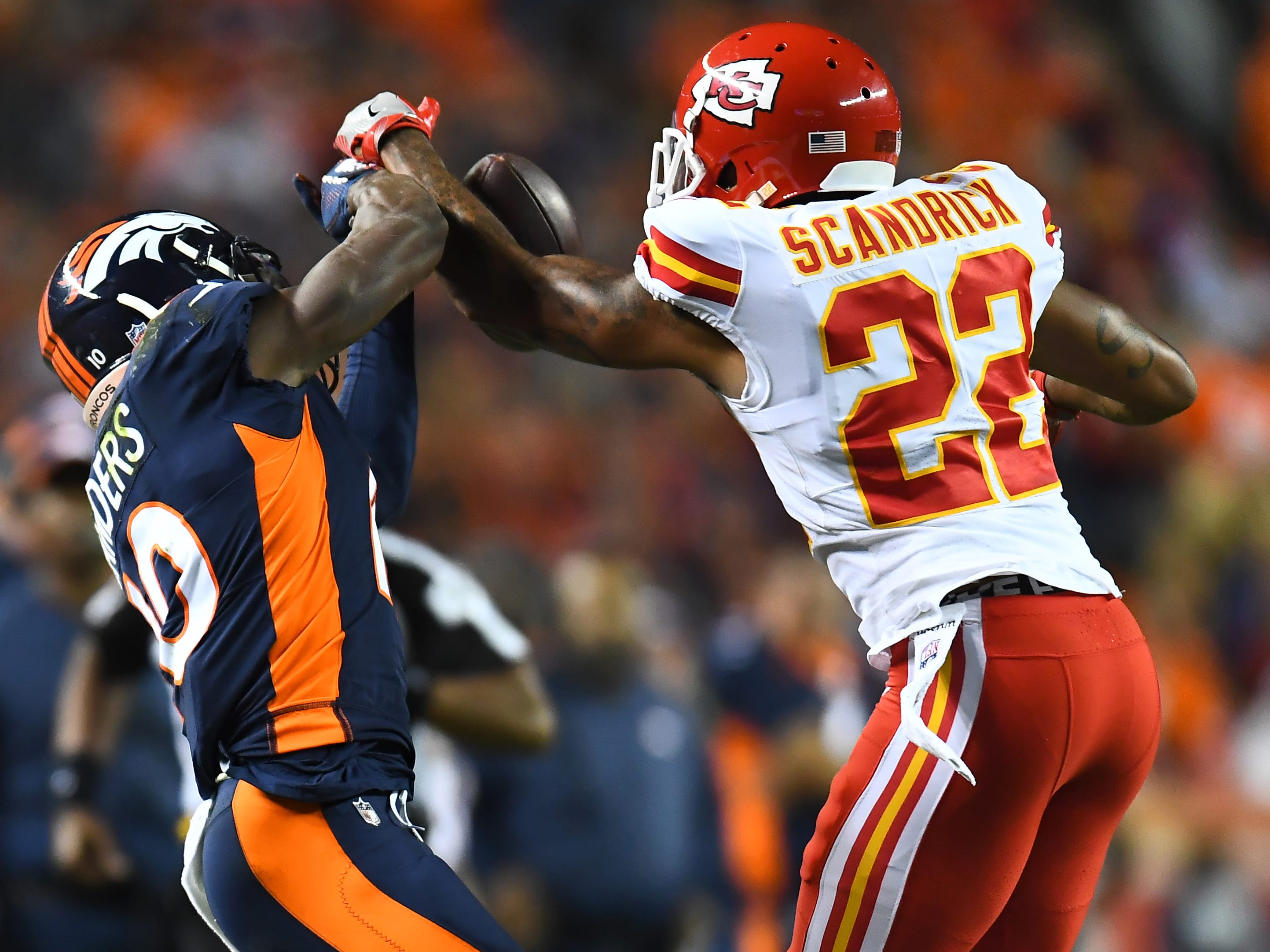 Kansas City Chiefs defensive back Orlando Scandrick breaks up a pass to wide receiver Emmanuel Sanders during the second quarter at Broncos Stadium at Mile High.