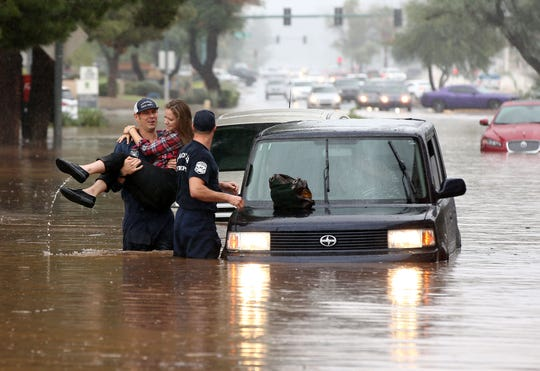 A Phoenix Firefighter rescues a woman from her car after being caught in flood waters that covered Tatum Blvd. north of Shea Blvd. in Phoenix, Ariz. The remnants of Hurricane Rosa is bringing heavy rain to central Arizona. Mandatory Credit: Rob Schumacher/The Republic via USA TODAY NETWORK