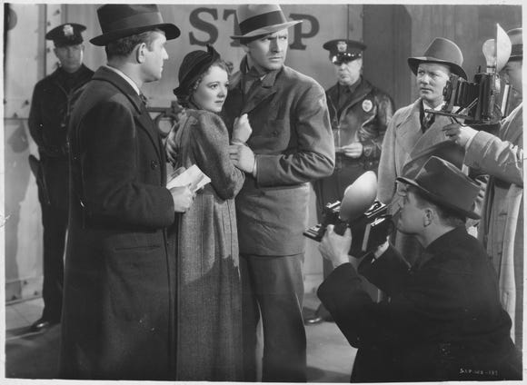 "Norman (Fredric March, center) protects Esther (Janet Gaynor) from paparazzi in 1937's ""A Star Is Born."""