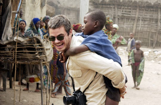 Scott Harrison, the founder and CEO of charity: water, interacts with residents of a village in Liberia.