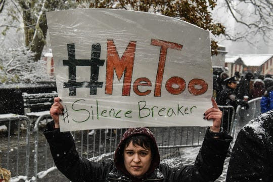 People carry signs addressing the issue of sexual harassment at a #MeToo rally outside of Trump International Hotel on December 9, 2017.