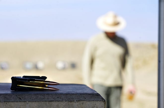 Benjamin White-Patarino walks back to his shooting position after adjusting his target at the Baker Draw shooting range on the Pawnee National Grassland about 90 minutes north of Denver. White-Patarino shoots a M-1 Garand, a WWII-era rifle chambered in .30-06 rounds, which are sitting on the table.