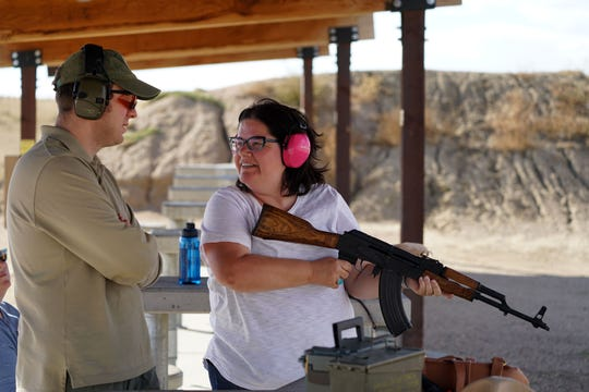 Competitive target shooter Benjamin White-Patarino chats with family friend Jackie Turner of Ontario, Canada, after she fired several shots from an AK-47 style rifle at the Baker Draw target range on the Pawnee National Grassland about 90 minutes north of Denver.