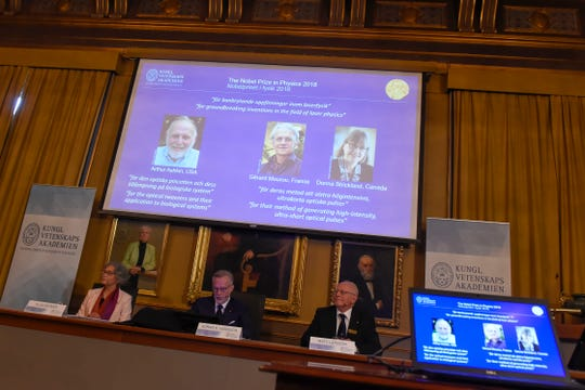 Members of the Nobel Committee for Physics, from left, Olga Botner, Goran K Hansson and Mats Larsson, sit in front of a screen displaying portraits of Arthur Ashkin of the United States, Gerard Mourou of France and Donna Strickland of Canada during the announcement of the winners of the 2018 Nobel Prize in Physics at the Royal Swedish Academy of Sciences on October 2, 2018 in Stockholm.