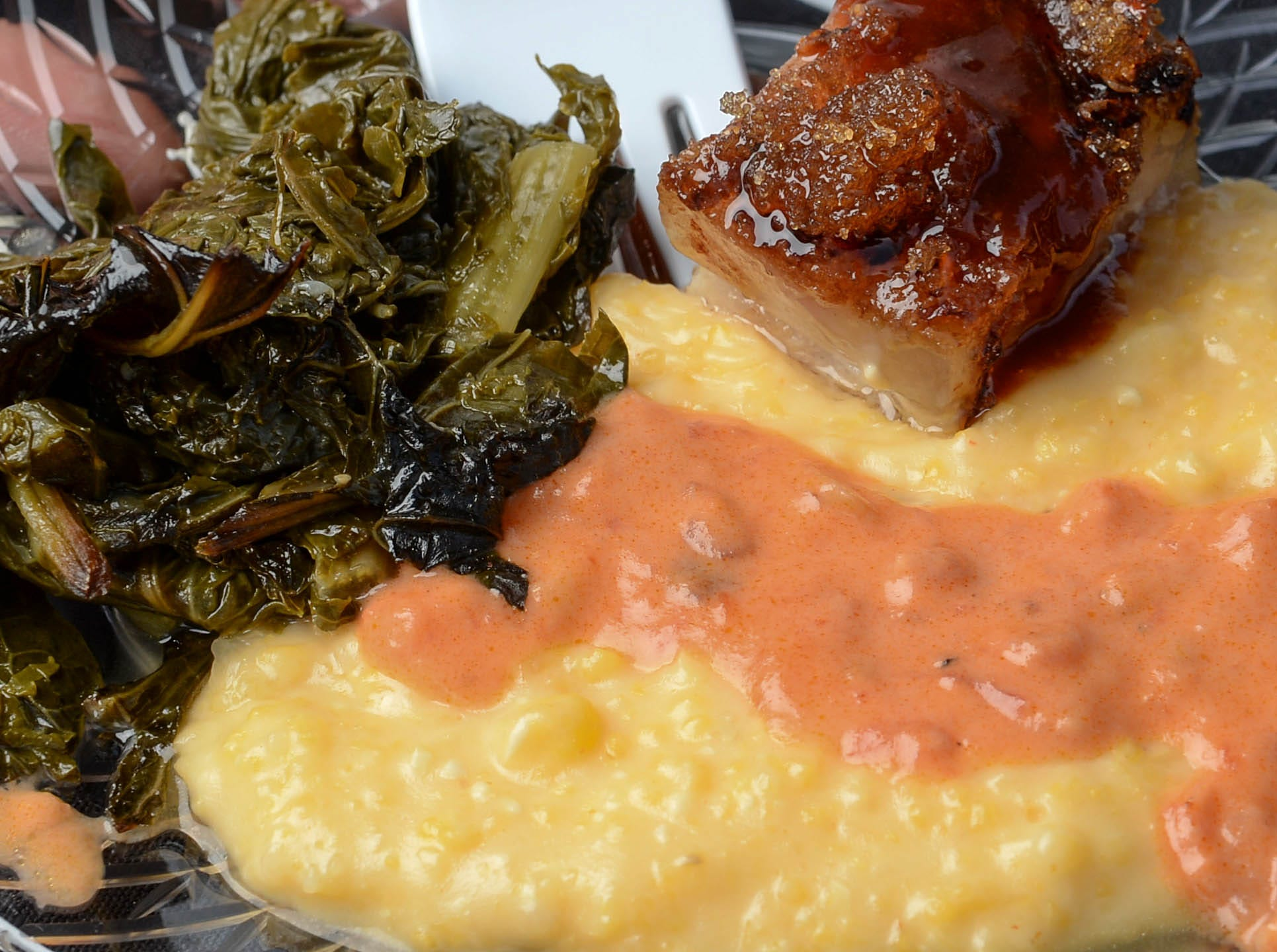 A sweet and smoky pork belly cheddar corn grits, tomato gravy and braised greens dish, a combination of Doolittle's and Greenbrier Farm at FreshTaste at Carolina Wren Park in downtown Anderson on Tuesday. The event showcases local food and emerging artists with special wine and craft beer tastings. The event is presented by the City of Anderson, with bluegrass music is by My Girl, My Whiskey, and Me!
