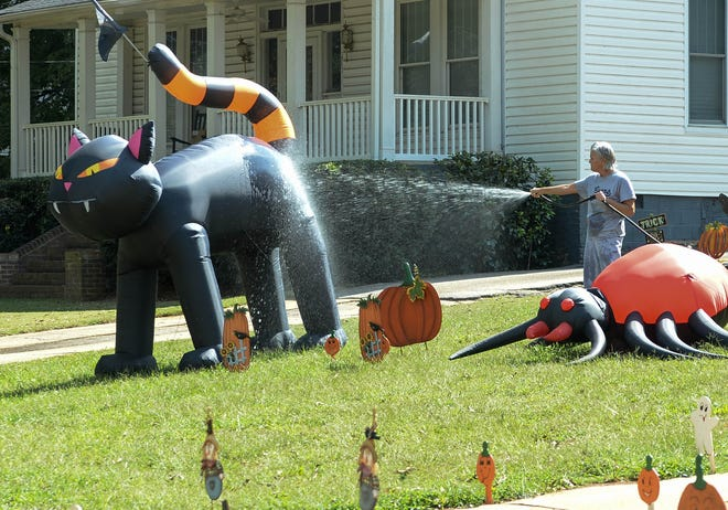 Terry Bruce of Pelzer waters plants and sprays down some of her decorations for halloween on S.C. 8 in Pelzer on Wednesday. Bruce said it was fun decorating for halloween and Christmas.