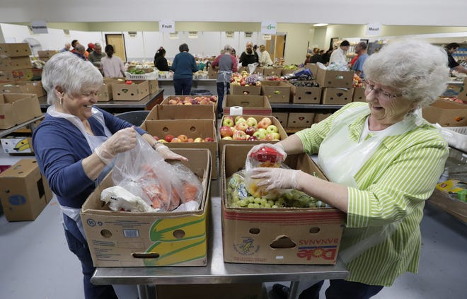 Volunteers Jean Mittag, left, of Appleton and Judy Belling of Neenah share a laugh while sorting a variety of fruit Oct. 1 at St. Joseph Food Program in Menasha. Dan Powers/USA TODAY NETWORK-Wisconsin
