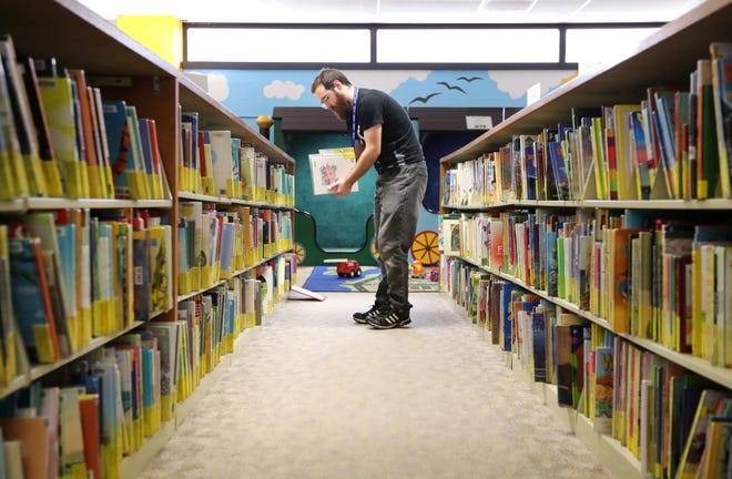 Tony Skoviak, a page clerk with the Appleton Public Library, puts children's books back on the shelf Wednesday.