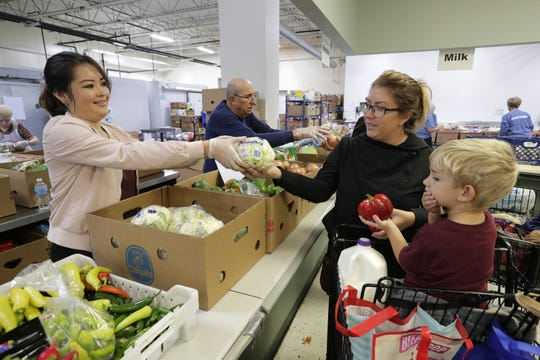 Post-Crescent reporter Mica Soellner, left, provides vegetable options for Audree Parker of Appleton and her son, Oliver, 3, during a volunteer shift Oct. 1 at St. Joseph Food Program in Menasha. Dan Powers/USA TODAY NETWORK-Wisconsin
