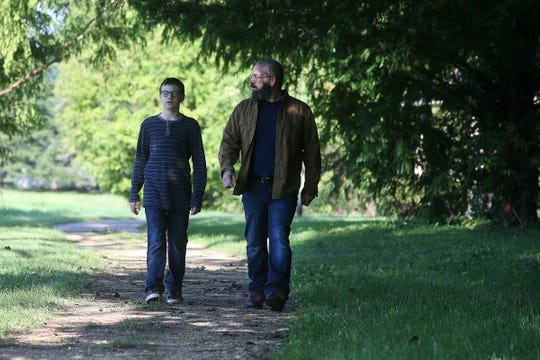 Joseph Vulpis, owner of Ultimate Outdoor Adventures, a Middletown business which promotes outdoor adventure and education, walks a trail with his 13-year-old son, Joseph, in Thompson Park in Lincroft, NJ Wednesday, October 3, 2018.