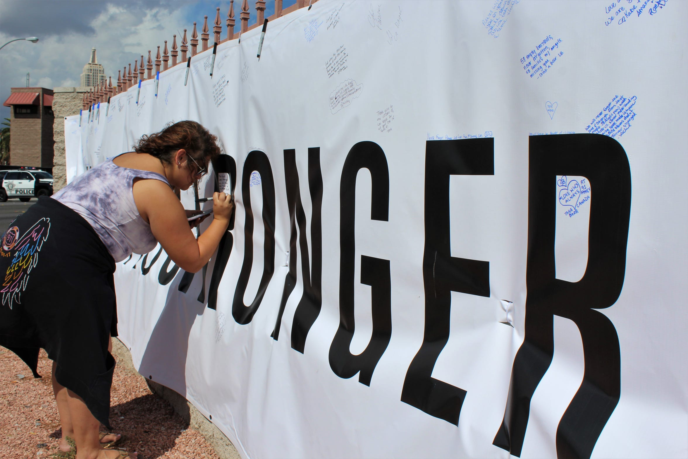 A woman pens a message on a banner across the street from the site of a 2017 shooting that killed 58 in Las Vegas.