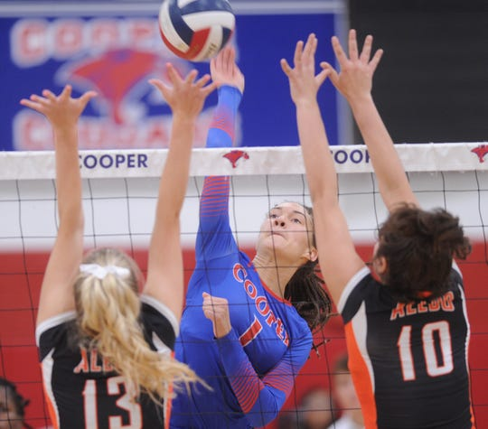 Cooper's Alexis Garcia (1) hits between Aledo's Anna Rogers (13) and Anastasia Morrison (10) during the third game of their match. Aledo beat the Lady Cougars 25-20, 25-10, 25-21 in the District 4-5A match Tuesday, Oct. 2, 2018, at Cougar Gym.
