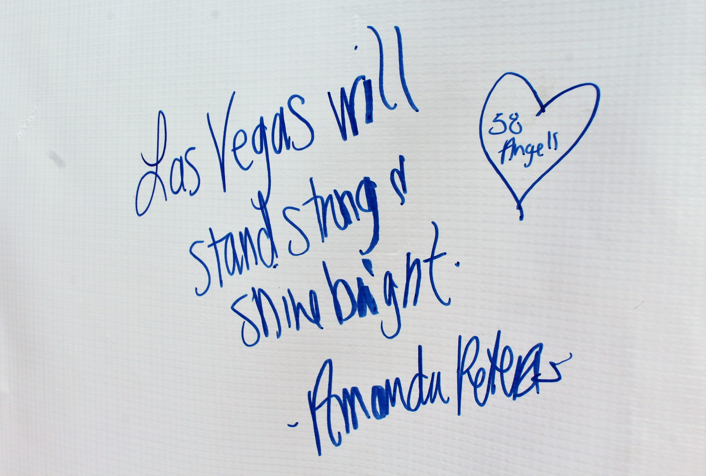 A message written on a banner Monday across the street from where 58 people attending a country music festival were killed in Las Vegas.