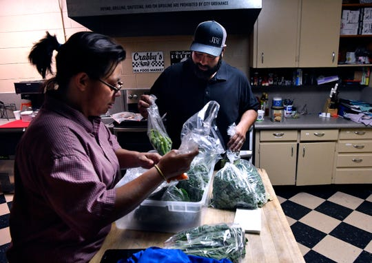 Anne McLean, the kitchen coordinator at Faithworks of Abilene, and Zacheri Espinoza sort the produce he brought to her Sept. 28. The food is from Nine Springs Garden, a Big Country farm business, for whom Espinoza works.