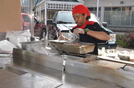 Adrian Longsworth, the new head chef of both the yet-to-open Current Kitchen & Bar as well as Springbrook Italian Bistro and Tap House, prepares food for customers at the Battle Creek Farmers Market on Wednesday, Oct. 3, 2018.