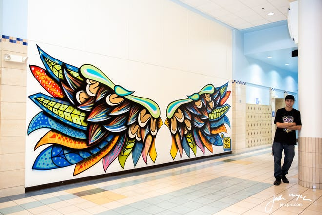 Artist Jars One stands next to his wing mural at Lakeview Square Mall.