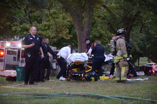 Paramedics and firefighters remove a woman who was badly injured from a burning house Tuesday, Oct. 2, 2018