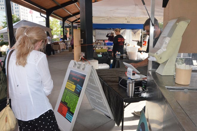 Visitors to the Battle Creek Farmers Market try out some of Current Kitchen & Bar's future menu on Wednesday, Oct. 3, 2018.