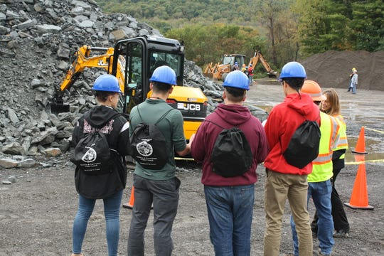 Students from Sidney High School look on as Wyatt Kiff, 16, of Sidney, operates a mini excavator during Wednesday morning's Construction and Technology Career Day.