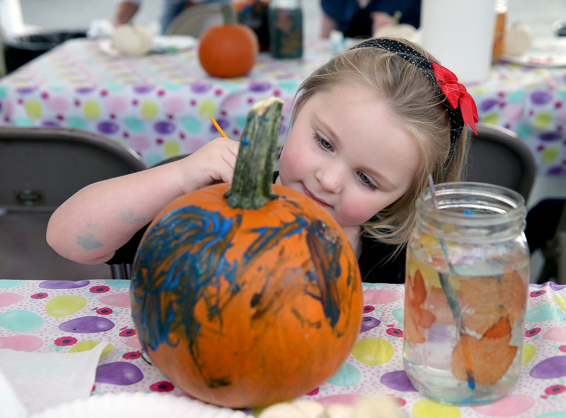 Iris Eckstrom, 4, of Bremerton paints a pumpkin at the Central Kitsap Farmers Market in Old Town Silverdale on Tuesday, October, 2, 2018.The pumpkins were supplied by Pheasant Fields Farm in Silverdale.