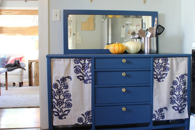 A buffet repainted a deep blue and shelves above it give a more pleasing look with an industrial-style flooring.