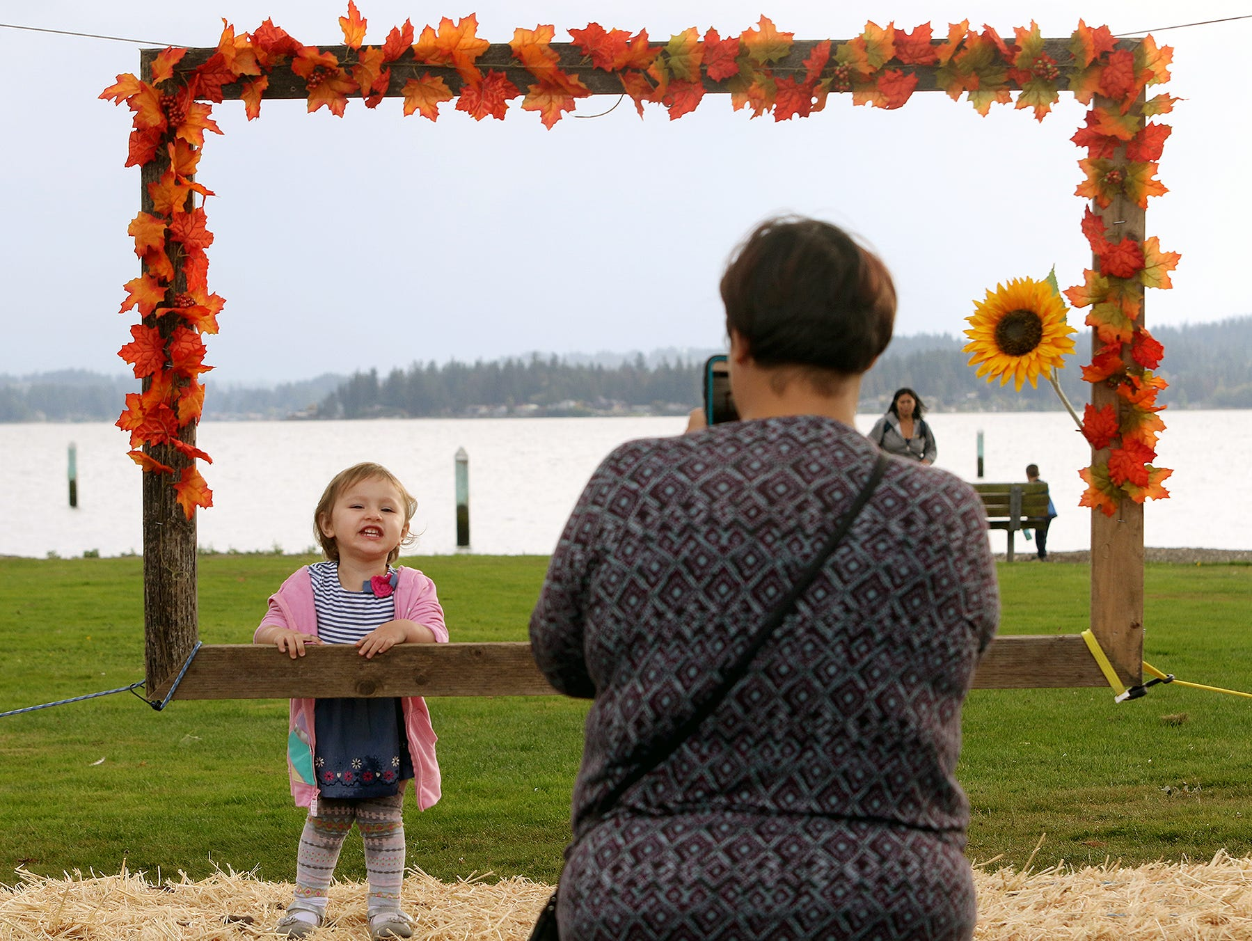 Patterson Goodwin, 2, says cheese as he mom Maria takes her picture in a fall photo frame after she painted a pumpkin at the Central Kitsap Farmers Market in Old Town Silverdale on Tuesday, October, 2, 2018.The pumpkins were supplied by Pheasant Fields Farm in Silverdale.