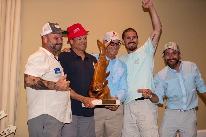 Tournament winner Roger Fernandez, red hat, and his guide Capt. Steven Tejera, arm raised, celebrate at the Herman Lucerne Championship awards dinner. Others, from left, are David Wirth who sculptured the trophy; Dr. Lloyd Wruble, tournament chairman; and Dave Chouinard, the awards MC. Fernandez became the first fly fisherman to win the benefit tournament in its 19-year history.