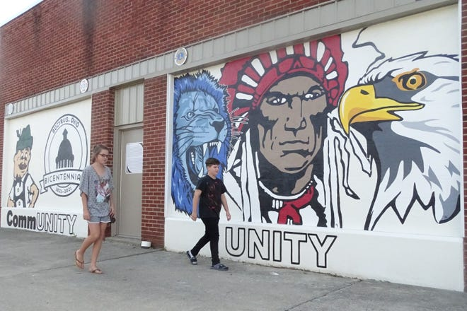 """Johanna Williams, 14, and Izzy Amrine, 10, both of Bucyrus, walk by the city's new """"Community Unity"""" mural."""