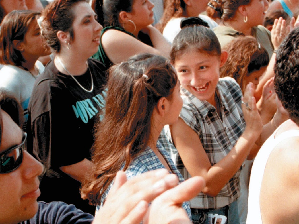 Valerie Rodriguez,15, (right) talks to her friend, Elizabeth Trevino,15, while dancing to Fandango USA at Freddie Fest at Texas Sky Festival Park in Corpus Christi on Aug. 24, 1997.